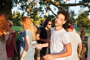 Portrait of mid adult man at crowded sunset party in parkの写真素材 [FYI03536925]
