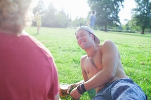 Adult friends relaxing at sunset park partyの写真素材 [FYI03536964]