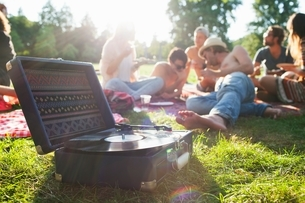 Adult friends relaxing and listening to record deck at sunset park partyの写真素材 [FYI03537009]