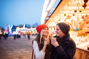 Young couple drinking mulled wine at Xmas festival, Hyde Park, London, UKの写真素材 [FYI03537258]