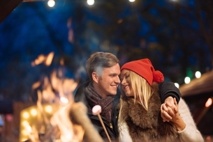 Romantic young couple toasting marshmallows at xmas festival in Hyde Park, London, UKの写真素材 [FYI03537262]