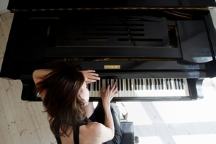 Overhead view of mature woman leaning on piano playingの写真素材 [FYI03537298]