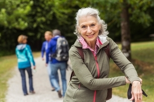 Portrait of senior woman on pathway in forestの写真素材 [FYI03537334]