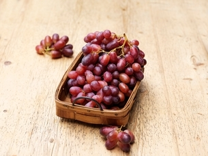 Red grapes in vintage wicker basketの写真素材 [FYI03537360]