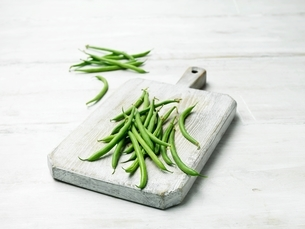Extra fine green bean on wooden chopping boardの写真素材 [FYI03537364]
