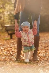 Portrait of baby girl holding mothers hands in autumn parkの写真素材 [FYI03537524]