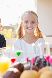 Portrait of happy girl with birthday cake at patio tableの写真素材 [FYI03537566]