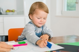 Female toddler using eraser whilst drawing at kitchen tableの写真素材 [FYI03537586]