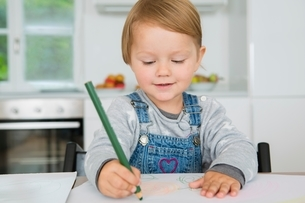 Female toddler drawing at kitchen tableの写真素材 [FYI03537587]
