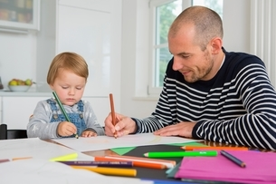 Mid adult man and toddler daughter drawing at kitchen tableの写真素材 [FYI03537588]