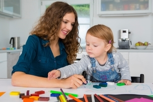 Teenage girl and female toddler drawing at kitchen tableの写真素材 [FYI03537589]