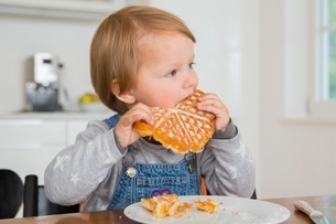 Cute female toddler eating cake at kitchen tableの写真素材 [FYI03537591]