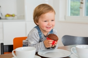 Cute female toddler holding cupcake at kitchen tableの写真素材 [FYI03537592]