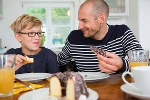 Mid adult man and son eating cake at kitchen tableの写真素材 [FYI03537597]
