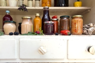 Jars and bottles of home-made food on retro style kitchen cabinetの写真素材 [FYI03537799]