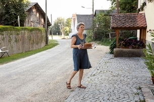 Mature woman across pathway, carrying tray with cake and drinksの写真素材 [FYI03537821]