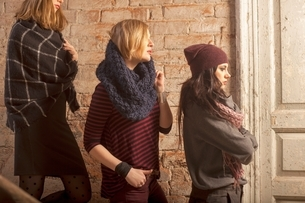 Side view of women wearing knitwear standing on stairs in front of brick wall looking awayの写真素材 [FYI03537921]
