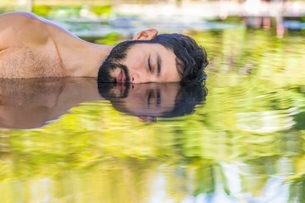 Bearded young man lying on side in water, illusion of mirror image, Taiba, Ceara, Brazilの写真素材 [FYI03537979]