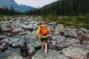 Rear view of mid adult man carrying backpack walking on rocky riverbed, Moraine lake, Banff Nationalの写真素材 [FYI03538189]
