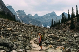 Side view of mid adult woman on rocky landscape beneath mountain range, Moraine lake, Banff Nationalの写真素材 [FYI03538200]