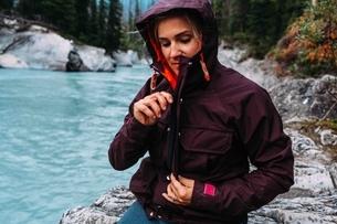 Mid adult woman by waters edge zipping up waterproof coat, Moraine lake, Banff National Park, Albertの写真素材 [FYI03538217]