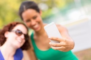 Young women using smartphone to take sefie smiling, focus on foregroundの写真素材 [FYI03538308]