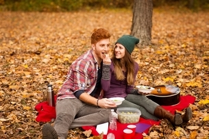 Young couple having picnic in autumn forestの写真素材 [FYI03538411]