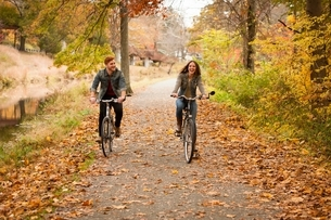 Happy young couple cycling on riverside in autumnの写真素材 [FYI03538429]