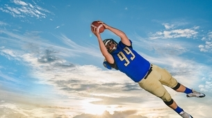 Male teenage American football player catching ball mid air against blue skyの写真素材 [FYI03538553]