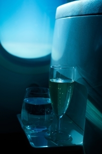 Champagne flute and tumbler in front of airplane windowの写真素材 [FYI03538741]