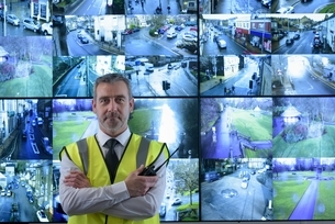Portrait of security guard in front of in video wall in security control roomの写真素材 [FYI03538804]