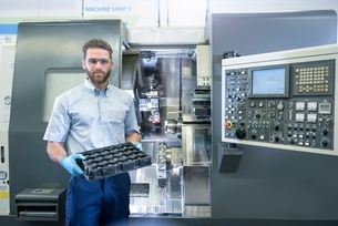 Portrait of engineer with CNC lathe in automotive parts factoryの写真素材 [FYI03538828]