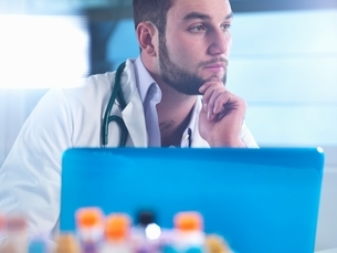Doctor thinking about patient medical test results, samples in foregroundの写真素材 [FYI03538861]