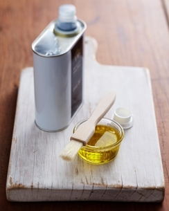 Bowl of olive oil and pastry brush on wooden chopping boardの写真素材 [FYI03538895]