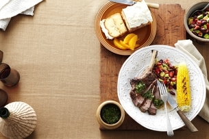 Overhead view of South American dinner with plate of steak, corn, kidney bean salad and salsa verdeの写真素材 [FYI03538937]