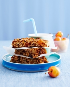 Stack of muesli flapjacks, drink with bowl of cherries, kids lunch ideaの写真素材 [FYI03538994]