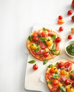 High angle view of tomato, basil and prosciutto pizzas on cutting boardの写真素材 [FYI03539031]
