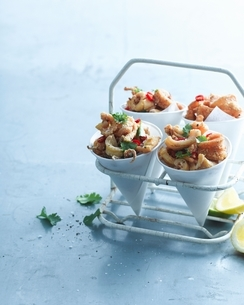 Salt and pepper chilli squid garnished with lemon and coriander in paper conesの写真素材 [FYI03539032]