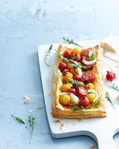Overhead view of tomato and parmesan puff pastry tart garnished with rocket on cutting boardの写真素材 [FYI03539036]