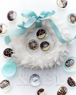 Overhead view of coconut creams in cake cases around feather wreath tied with bowの写真素材 [FYI03539039]