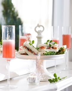 Champagne flutes of pink champagne and crayfish sandwiches on cake standの写真素材 [FYI03539040]