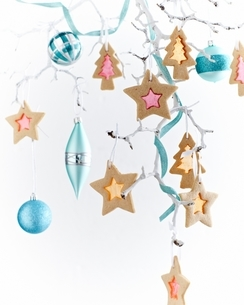Star shaped stained glass biscuits and baubles hanging from painted white branchの写真素材 [FYI03539041]