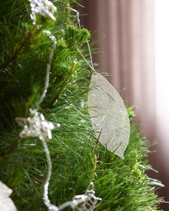 Close up of feather christmas decoration hanging from christmas treeの写真素材 [FYI03539047]