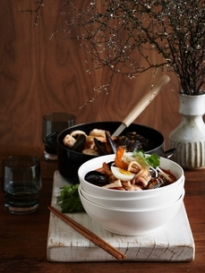 Seafood laksa in stacked bowl on whitewashed cutting boardの写真素材 [FYI03539068]