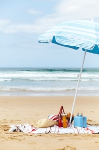 Sunhat, cool box and picnic basket on beach towel underneath parasol on beachの写真素材 [FYI03539080]
