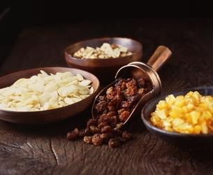Chopped hazelnuts, raisins and dried orange in bowlsの写真素材 [FYI03539265]