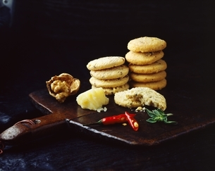 Stacks of homemade walnut chilli cheese oatcakes on vintage wooden trayの写真素材 [FYI03539278]