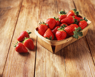 Punnet of strawberries on wooden tableの写真素材 [FYI03539343]
