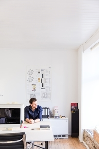 Mid adult man sitting at desk in office looking out of windowの写真素材 [FYI03539411]