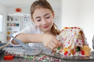 Girl at kitchen counter decorating ginger bread house smilingの写真素材 [FYI03539515]